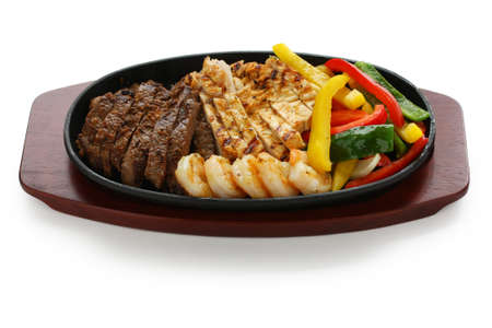 sizzling: beef chicken and shrimp fajitas Stock Photo
