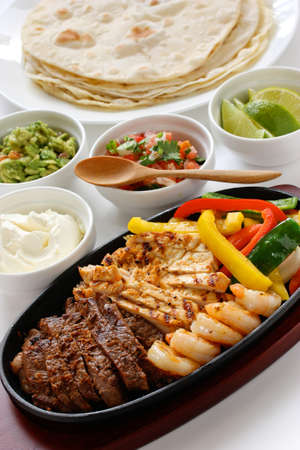 sizzling: beef chicken and shrimp fajitas, mexican cuisine Stock Photo