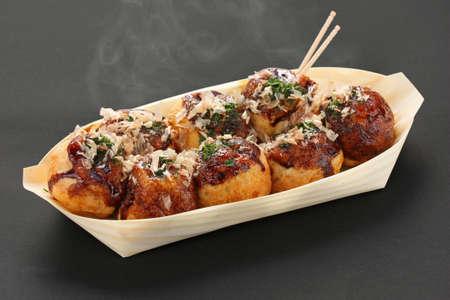 comida japonesa: takoyaki, bolas de pulpo, comida japonesa, sobre un fondo negro Foto de archivo