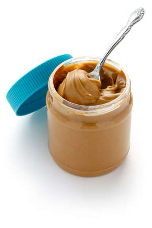 peanut butter: an open jar of peanut butter with spoon