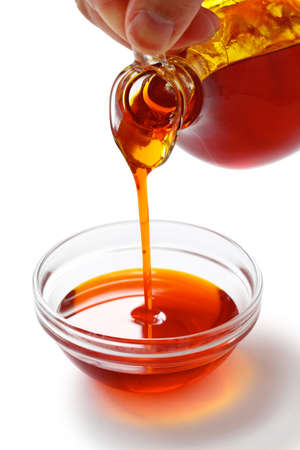 cooking oil: pouring red palm oil into a glass bowl