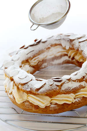 profiterole: sifting powdered sugar over a paris brest.