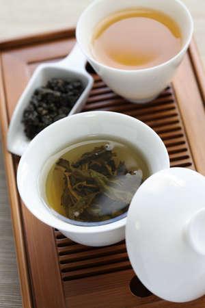 hojas de te: ceremonia tradicional de t� chino, t� oolong, gaiwan, degustaci�n de taza, bandeja de t� de bamb� Foto de archivo