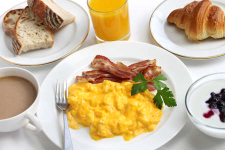 bacon and eggs: breakfast with scrambled eggs, crispy bacon, croissant,yogurt, orange juice and cafe au lait Stock Photo
