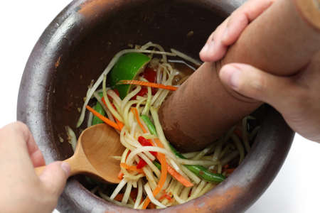 making of green papaya salad, som tam, thai food, ingredients are mixing and pounding in a mortar   photo