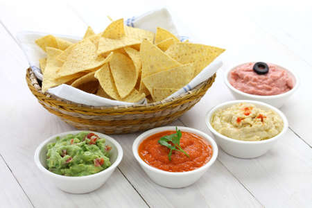 tortilla chips with four dips, which are salsa roja, guacamole, taramasalata, and hummus
