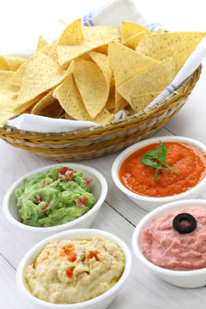 football party: tortilla chips with four dips, which are salsa roja, guacamole, taramasalata, and hummus