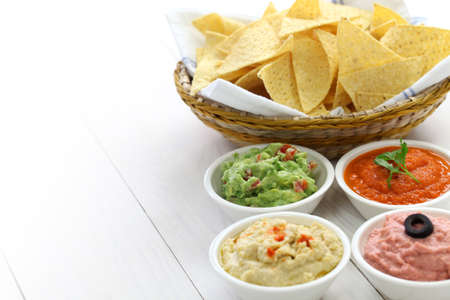 american food: tortilla chips with four dips, which are salsa roja, guacamole, taramasalata, and hummus