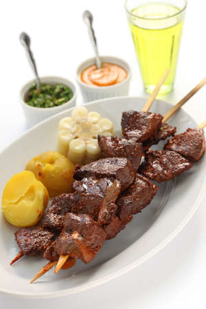 barbecued: anticuchos, Peruvian cuisine, grilled skewered beef heart meat with boiled potato and white corn