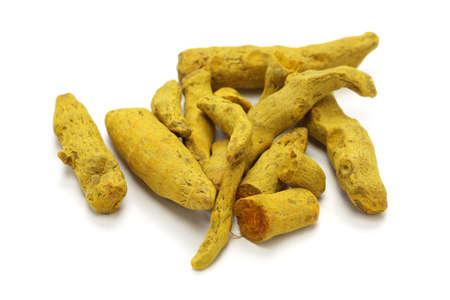 dried whole turmeric on white  photo
