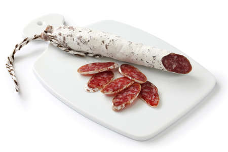 embutido: fuet calidad, spanish moldy salami on white cutting board Stock Photo