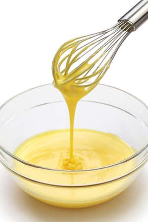 whisking: whisking egg yolks and sugar in a bowl, making custard cream process
