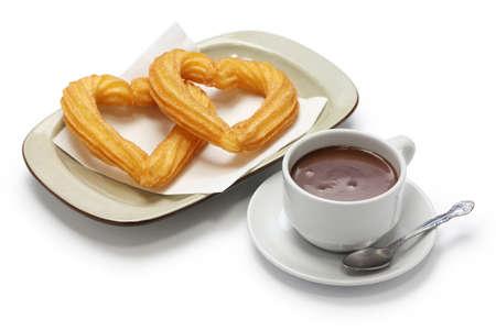 heart shape churros and hot chocolate on white background photo