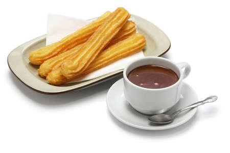 churros en warme chocolademelk op een witte achtergrond, spaans ontbijt Stockfoto