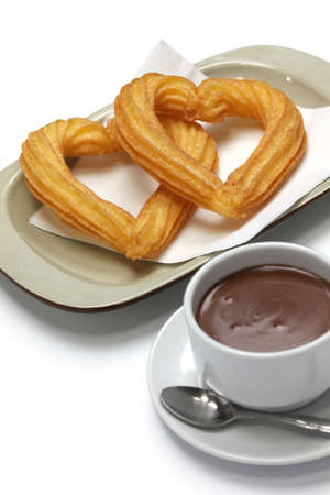 churros: heart shape churros and hot chocolate on white background