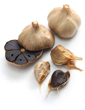 black garlic bulbs and cloves on white background Foto de archivo