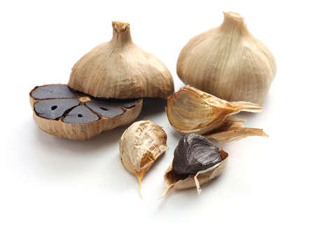 garlic: black garlic bulbs and cloves on white background Stock Photo