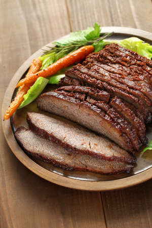 food state: barbecue beef brisket isolated on brown wood board