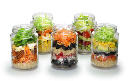homemade vegetable salad in glass jar on white background, no lid 스톡 콘텐츠
