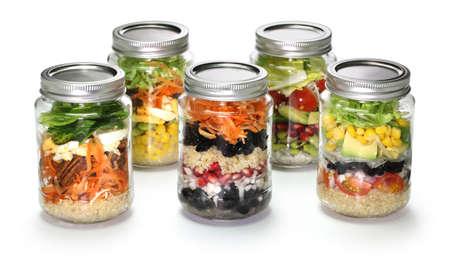 ensalada tomate: ensalada de verduras casero en frasco de vidrio en el fondo blanco Foto de archivo