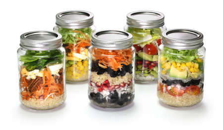 spinach salad: homemade vegetable salad in glass jar on white background