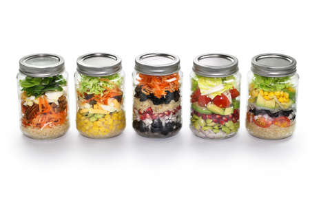 jars: homemade vegetable salad in glass jar on white background