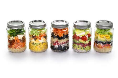 zelfgemaakte plantaardige salade in glazen pot op een witte achtergrond