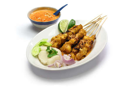 Satay de pollo con salsa de cacahuete, cocina pincho indonesio aislado en fondo blanco Foto de archivo - 37620449
