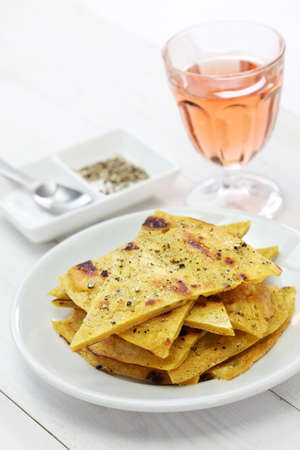 socca: socca, farinata, chickpea pancake with rose wine Stock Photo