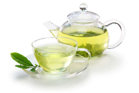 sklářských šálkem japonského zeleného čaje a konvici na bílém pozadí