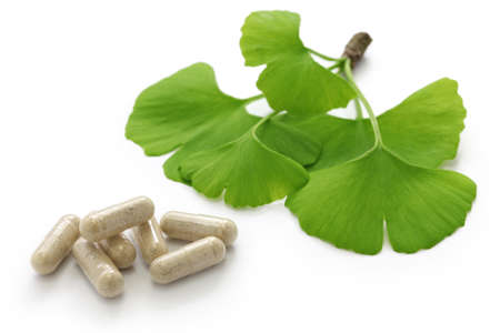 ginkgo biloba leaves and medicine capsule pills on white background Stock Photo