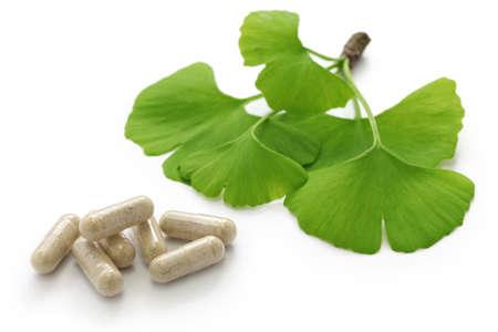 medicina tradicional china: hojas de ginkgo biloba y píldoras de la cápsula de medicina en el fondo blanco Foto de archivo