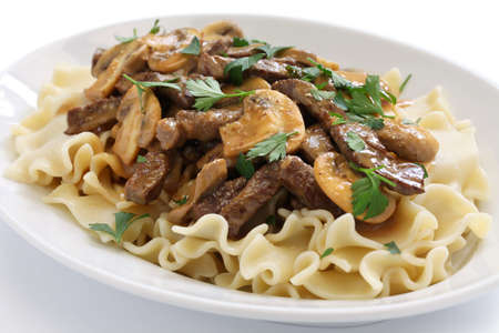 beef stroganoff with pasta russian cuisine isolated on white background