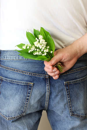 gift behind back: Man hiding bouquet of lily of the valley on his back