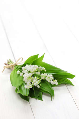 muguet: lily of the valley posy isolated on white wooden background