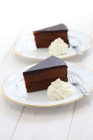 austrian: homemade sachertorte Austrian chocolate cake isolated on white wooden background Stock Photo