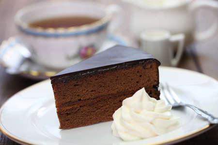 trozo de pastel: sachertorte casera pastel de chocolate austr�aca y t� Foto de archivo