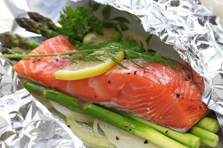 cooking food: fresh salmon with asparagus in foil paper ready for cooking