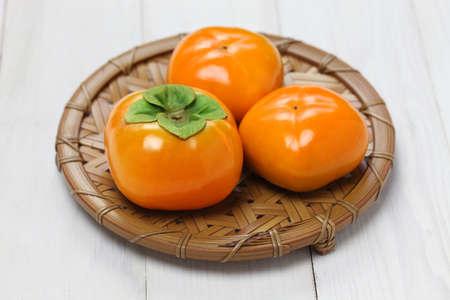 japanese people: Jiro kaki, japanese persimmon isolated on white wooden background