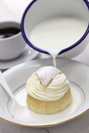 fat tuesday: semla in a bowl of warm milk, hetvagg Stock Photo