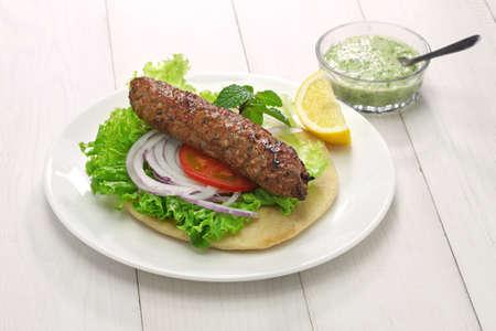 wraps: seekh cordero sándwich de kebab con chutney de menta Foto de archivo