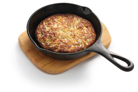 potatoes: Rosti, Swiss potato pancake in frying pan. Shredded potatoes sauteed on both sides until crisp and golden. Stock Photo