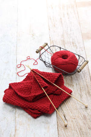 knitting needles: hand knitted red scarf, yarn ball and knitting needles, handmade christmas present Stock Photo