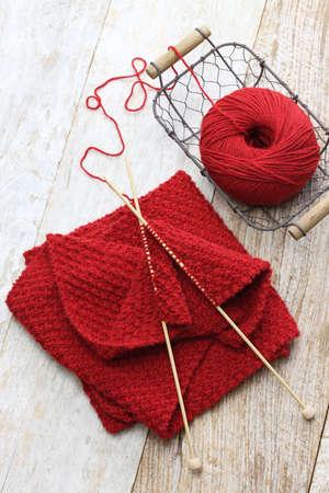 hand gebreide rode sjaal, garen bal en breinaalden, handgemaakt kerstcadeau Stockfoto