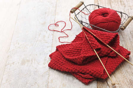 knitting: hand knitted red scarf and heart shaped thread