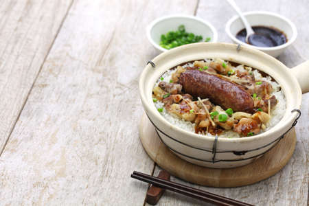 sausage pot: cantonese food, Chinese sausage and chicken with rice in clay pot Stock Photo