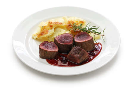 venison steak with creamy baked potato isolated on white background Stock Photo