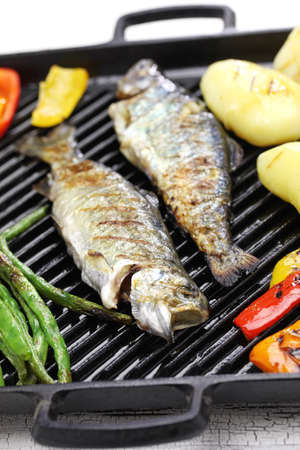 rainbow trout: grilled whole rainbow trout with vegetables on grill pan