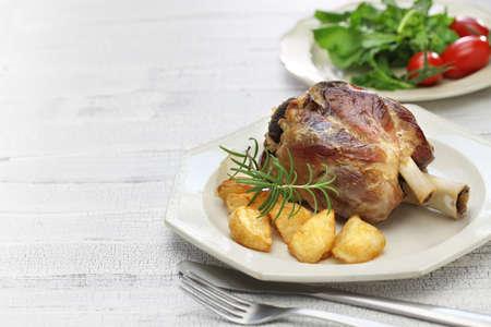 roast meat: pork shank with roasted potatoes, italian cuisine, stinco di maiale con patate arrosto