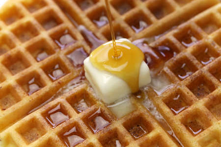 pouring maple syrup over homemade american round waffles with butter Stockfoto